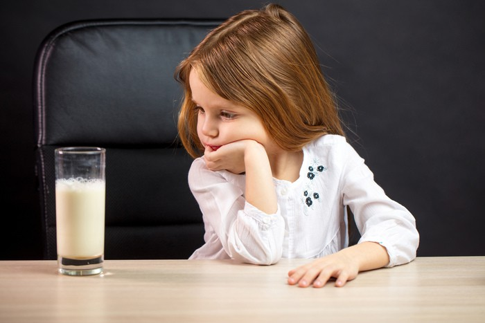 Gloomy little girl in glasses refusing to drink milk, over black