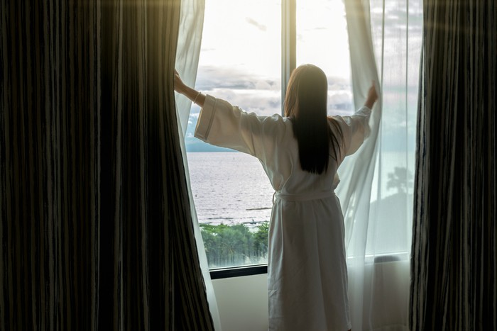 Back side of Asian woman in bathrope suit when waking up from the bed in luxury hotel in morning, Life style and holiday concept