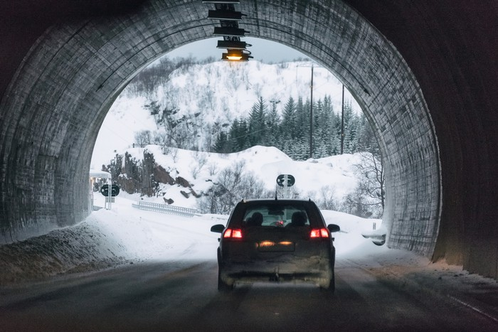 Rear car driving in mountain tunnel on winter