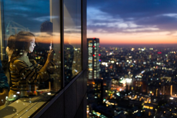 Woman visit the terrace and taking photo of the sunset in Tokyo city