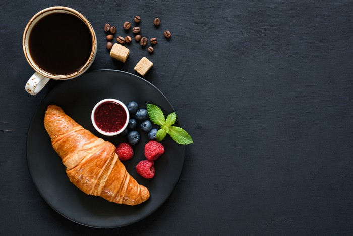 Croissant with berries, jam and cup of black coffee on black background