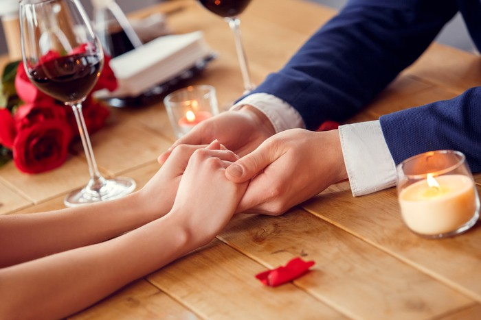 Young couple on date in restaurant sitting drinking wine holding hands close-up