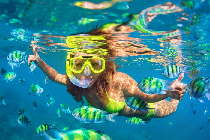 Girl in snorkeling mask dive with coral reef fish