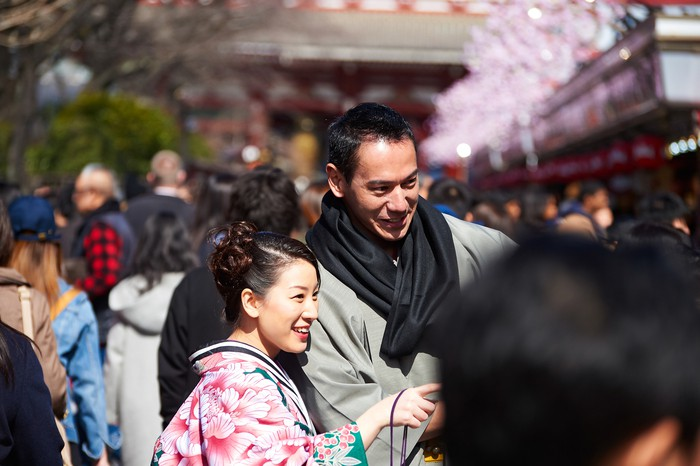 A happy couple wearing kimono is excited about something at downtown