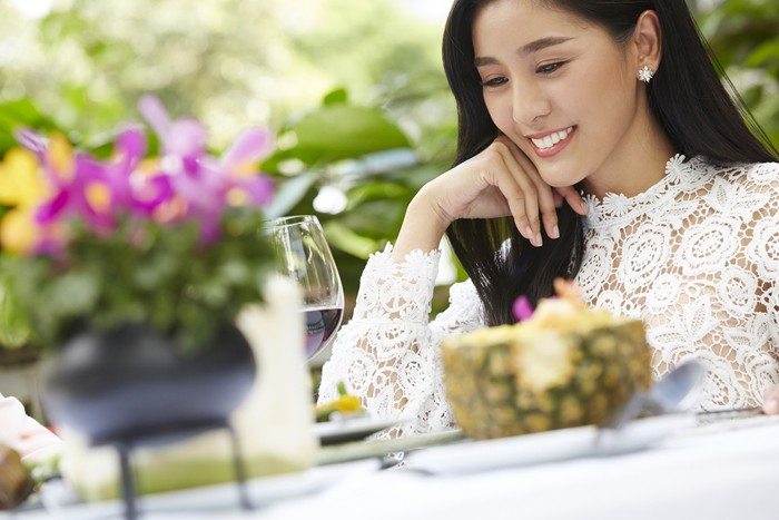 a gorgeous lady is smiling and looking at wine glass on a table in a restaurant