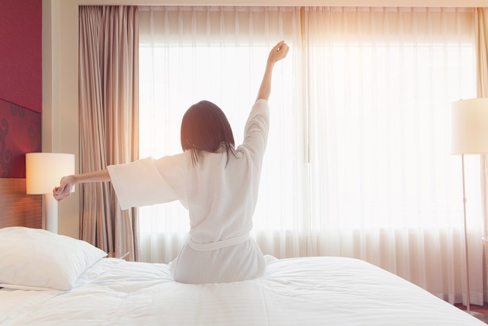 Woman stretching in bed after waking up, back