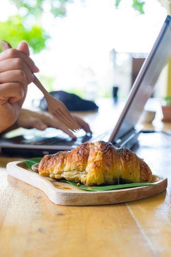 women using a fork to eat croissants
