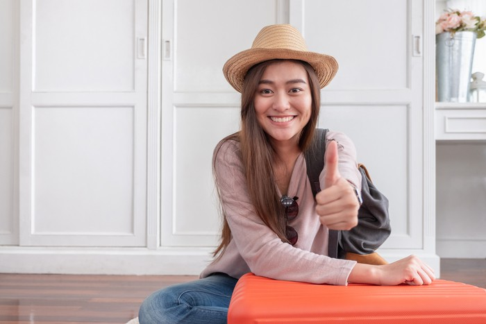 Young asian woman traveler thumbs up with orange