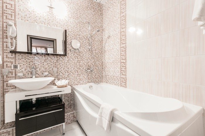 Clean white towel and bathrobe on a hanger prepared to use. Bathroom Inside rooms of a apartment or