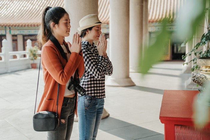 asian girls travelers pray at Buddhist temple