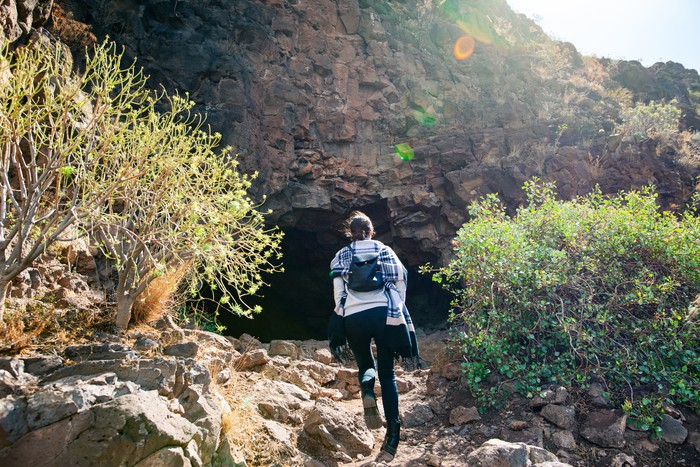 Hiker woman climbing to mountain cave
