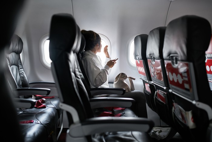 Woman with smartphone sits on black seat in plane