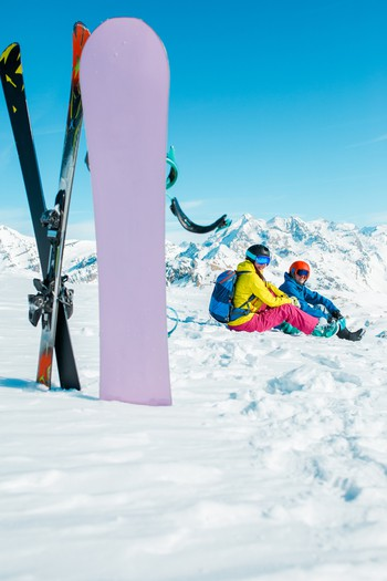 Photo of snowboard, skis on background of sitting