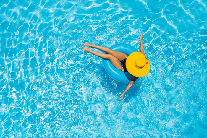 Woman sitting in a swimming pool on a ring pool float in a large yellow sunhat